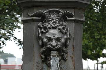 Fuente diablo / Fuente en parque con cabeza de diablo tallada en metaly agua saliendo por su boca.