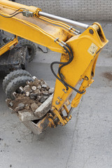 Yellow wheeled excavator carries dirt in a bucket.