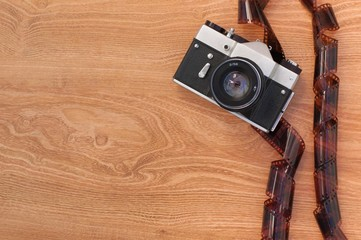 Old camera and negatives on a wooden background