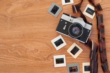 Vintage camera, slides and negatives on wooden background