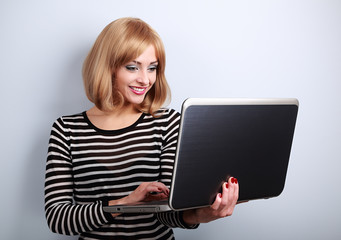 Happy casual woman holding and looking in laptop in hand and typ