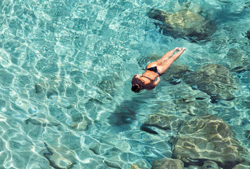 Top view of woman swimming at Milos, in Greece