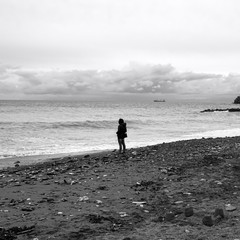 Girl standing in front of the sea. Black and white photo