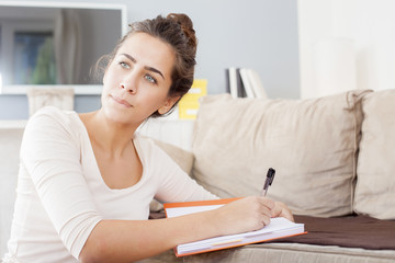 Pretty young woman sitting on her cozy bed and making notes to her diary,shallow depth of filed