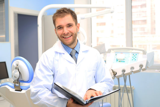 Dentist writes a patient a prescription in medical office