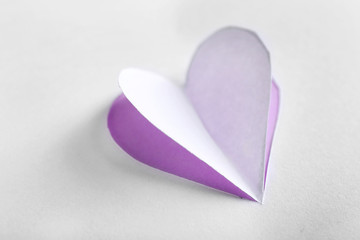 Cut out white paper heart on purple background