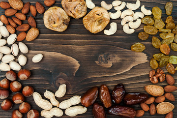 Mix of dried fruits and nuts on a dark wood background with copy space. Top view