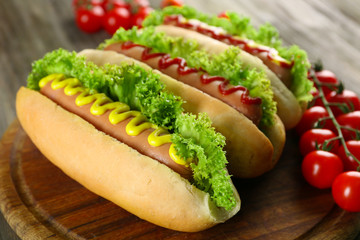 Tasty hot-dogs with tomatoes on wooden background
