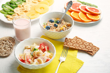 Tasty oatmeal and fruit salad on wooden background. Healthy eating concept.