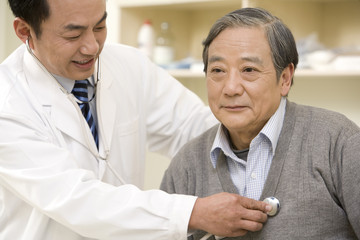 Male doctor examining patient with the stethoscope