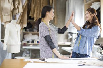 Two female fashion designers high fiving in studio