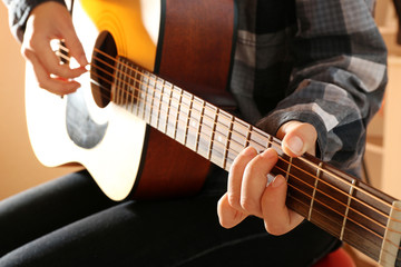 Guitarist plays guitar in the studio, close up