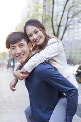 Young man piggybacking girlfriend