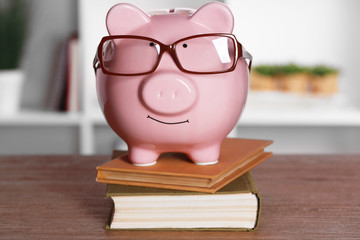 Piggy bank in glasses with books on home or office background