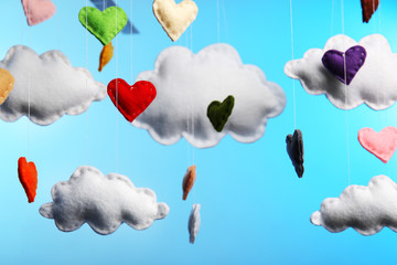 Fleece clouds and hearts on blue background