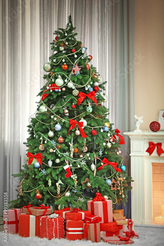Christmas Tree With Presents Near The Fireplace In A Room Stock
