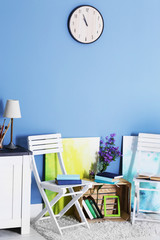 Room design with white furniture, bookcase, pictures, flowers and clock over blue wall