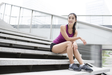 Young woman resting on the stairs after exercise