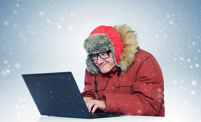 Programmer with a laptop in the winter blizzard