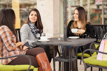 Women enjoying coffee in a cafe outdoors