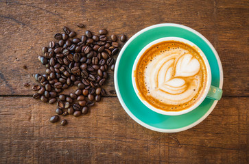 Latte hot coffee in green cup with latte art and roasted coffee beans. Wooden table background. Top...