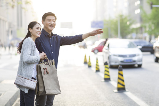 Happy mature couple waiting for a taxi