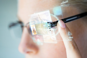 close up of woman in glasses with virtual screen Wall mural