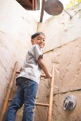 Little boy climbing up on ladder