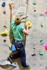 Mann klettert in einer Indoor-Kletterhalle die Wand hoch