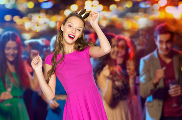 happy young woman in princess crown at night club