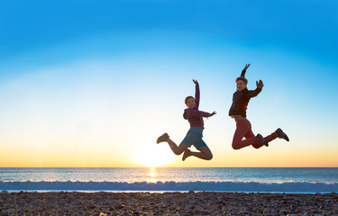 Girl and Guy jumping high with arms up spectacular sunrise at ocean coast