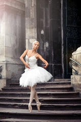 Motions of grace. Soft focus shot of a young female ballet dancer practicing on the stairway of an old building