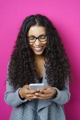 lachende frau schaut auf ihr smartphone