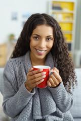 frau sitzt in ihrer wohnung und genießt eine tasse tee