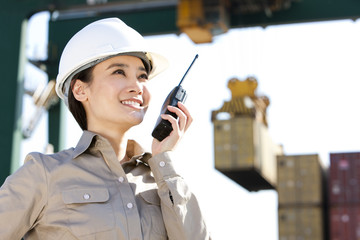shipping industry worker directing cranes with her walkie-talkie
