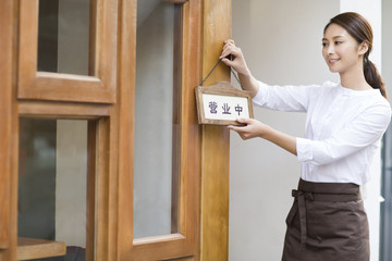 Young waitress with open sign in restaurant doorway