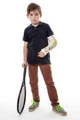 boy with cast on left arm and tennis racket