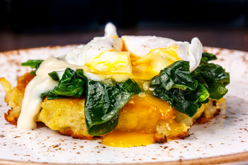 The poached egg on the cutlet from potatoes with spinach.