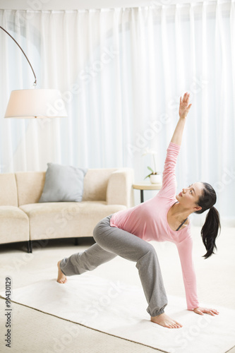 Young woman practicing yoga in living room stock photo for Living room yoga