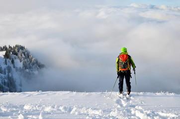 Mit Schneeschuh im Hochgebirge, Blick auf Nebel im Tal