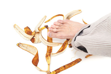 Bare foot in trousers on banana peel