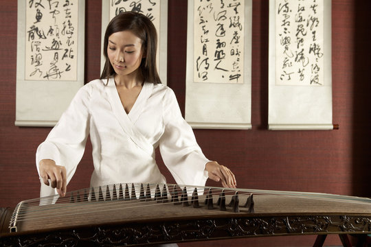 Young Woman Playing Traditional Chinese Instrument