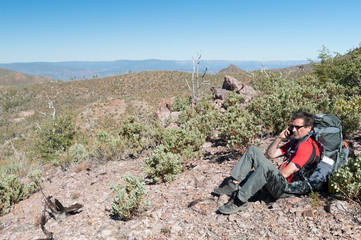 Male Caucasian long-distance hiker with a large backpack using his mobile phone in the Mazatzal Wilderness from a remote high point on the Arizona Trail, Arizona, US