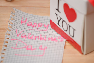 Card with Happy Valentines day and box on wooden background