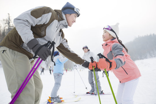 Young parents teaching children to ski