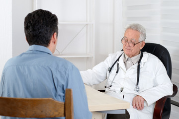 Male patient having consultation with old Doctor in consulting r
