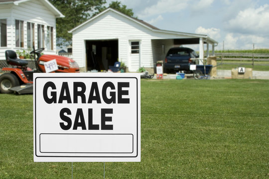 Yard and Garage Sale – A garage sale sign in the front yard of a home. Items for sale in the background.