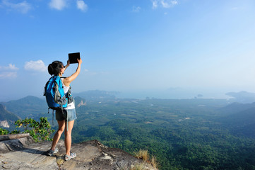 young woman hiker taking photo with digital tablet on mountain peak