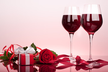 Valentine's decoration with rose, wine glasses, heart and gift boxes. Glossy red table top. Background slightly lit by red.
