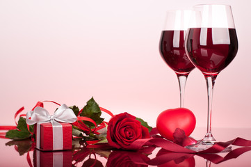 Valentine's decoration with wine glasses, rose,  heart and gift box. Glossy red table top. Background slightly lit by red.